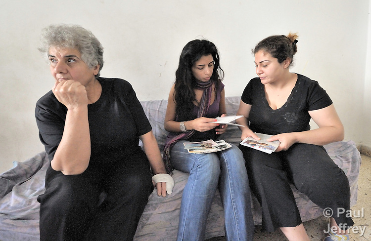 Rana Ramzi (right) shows photos of her dead husband to Ranha Chehab, a social worker of the Caritas Lebanon Migrant Center, in Ramzi's apartment in Beirut. Ramzi's husband was killed February 29, 2008, in Mosul, Iraq, while working as a driver and assistant to the Chaldean archbishop of Mosul, Archbishop Faraj Rahho, who was later found dead. Ramzi and her three children fled Iraq in May and live as refugees in Lebanon, along with Ramzi's mother (left), also a refugee from Iraq. They have received assistance from the Caritas Lebanon Migrant Center, which is funded by Catholic Relief Services, the relief and development agency of the U.S. Catholic community. Both Ramzi and her children and mother hope to resettle in the United States.