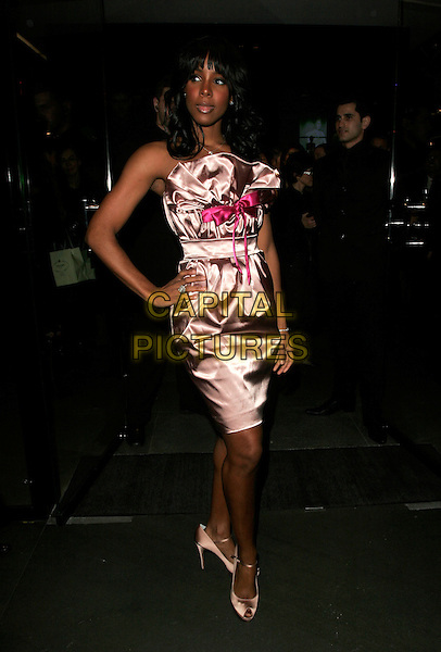 KELLY ROWLAND .Dolce & Gabbana Store, Old Bond Street, London, England. .December 13th, 2007.full length pink satin silk dress peep toe shoes ribbon bow strapless hand on hip too big large look closer.CAP/AH.©Adam Houghton/Capital Pictures.