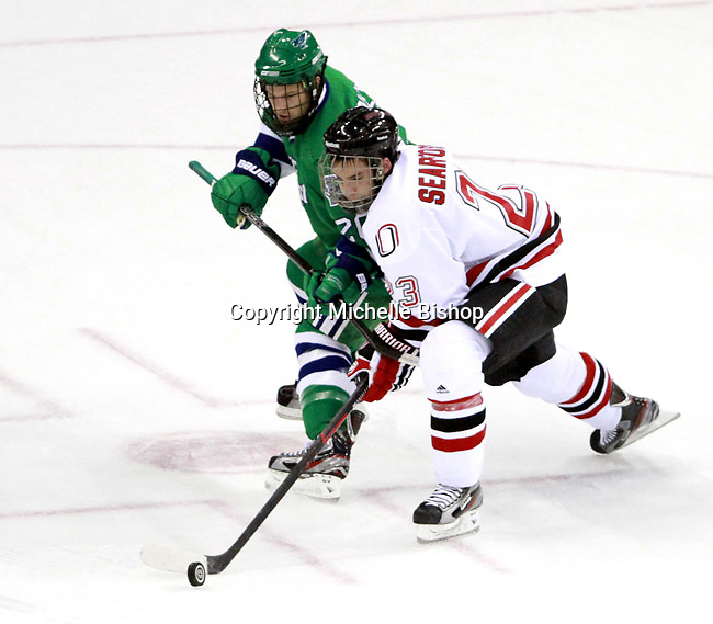 Nebraska-Omaha's Johnnie Searfoss and Mercyhurst's Grant Blakey battle for the puck. (Photo by Michelle Bishop) .