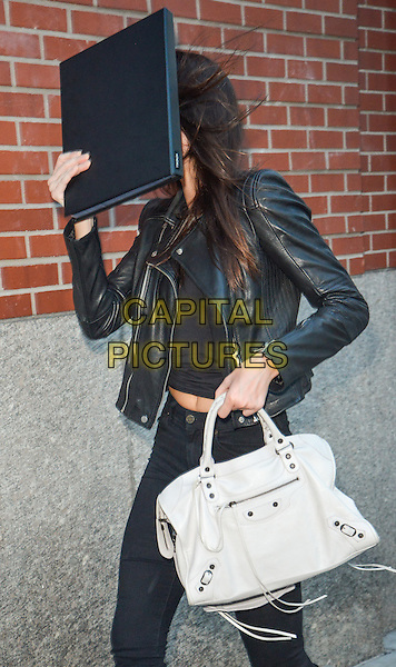 NEW YORK, NY - SEPTEMBER 1: Kendall Jenner hides her face with her modeling book in New York, New York on September 1, 2014. <br /> CAP/MPI67<br /> &copy;MPI67I/Capital Pictures