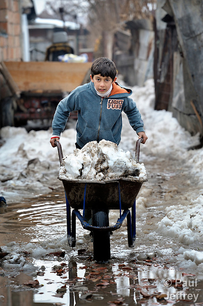 A boy pushes a wheel barrow full of snow in a Roma settlement in Belgrade, Serbia, as he helps his family clean up after a deadly cold spell in the Balkans.