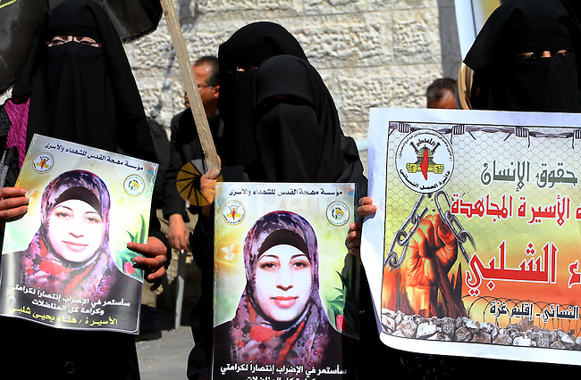 Palestinian women demonstrate in solidarity with Hana'a Shalabi during a protest in front of red cross in Gaza City, on mar. 07, 2012. Shalabi, released by Israel in a prisoner swap last year but re-arrested earlier this month and held without charge, is on a hunger strike to protest her treatment, officials said. The Arabic writing on the sign reads ''Down with administrative detentions'.  Photo by Ashraf Amra