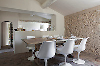The kitchen/dining area is furnished with Tulip chairs and a simple wooden table and features a signature wall of rough stone