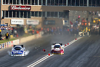Jul. 19, 2014; Morrison, CO, USA; NHRA funny car driver Tim Wilkerson (right) crosses over the centerline taking out the timing blocks alongside Tommy Johnson Jr during qualifying for the Mile High Nationals at Bandimere Speedway. Mandatory Credit: Mark J. Rebilas-