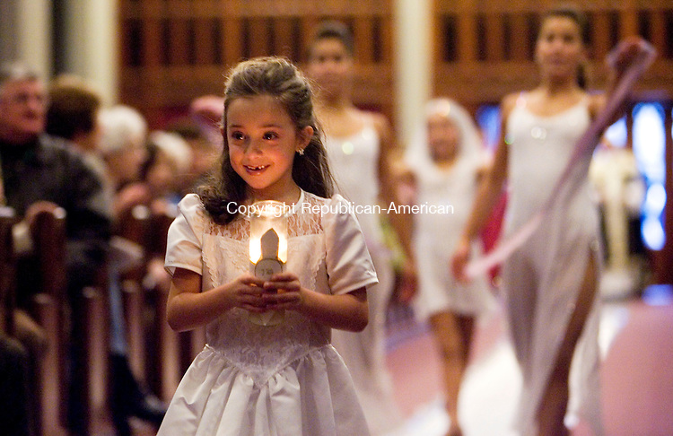 WATERBURY, CT- 06 JAN 2008- 010608JT08-<br /> Allie Maringola, playing a sprite, carries a lit candle up the aisle of the Shrine of Saint Anne in Waterbury during their third annual Boar's Head Festival on Sunday. Behind Allie are fellow sprites Bianca Vitale, Victoria Maringola, and Micah Vitale. <br /> Josalee Thrift / Republican-American