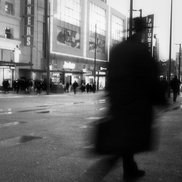 A blurred man in long black trench coat and hat walking down Granville Street in the rain.