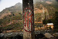 "Powerlines stretch over the mountains outside Xinjie in southern Yunnan Province, China.  ""Chai,"" the Manadarin character on the pole, indicates that the pole will soon be demolished."