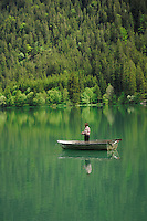 Fisherman in boat reflected in Lake Plansee near Reutte, Austrian Alps. Austria.