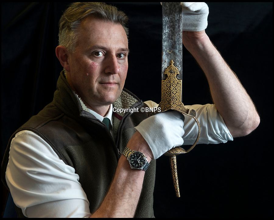 BNPS.co.uk (01202) 558833<br /> Pic: PhilYeomans/BNPS<br /> <br /> 'Once in a lifetime find' Auctioneer Anthony Cribb with the Tiger of Mysore's ornate gold encrusted sword.<br /> <br /> Stunning artefacts from Indian hero Tipu Sultan's fateful last stand have been rediscovered by the family of an East India Company Major who took part in the famous battle that ended his reign.<br /> <br /> And now Major Thomas Hart's lucky descendents are likely to become overnight millionaires after retrieving the historic items from their dusty attic.<br /> <br /> The fascinating treasures were taken from Tipu's captured fortress of Seringapatam in the wake of his defeat by British forces led by a young Duke of Wellington in 1799.<br /> <br /> The cache of ornate gold arms and personal effects even include's the battle damaged musket the Sultan used in his fatal last stand against the expanding British Empire in India.<br /> <br /> Tipu was last seen on the battlements of the fortress firing his hunting musket at the advancing British and after the fierce encounter his body was found bearing many wounds, including a musket ball shot above his right eye.<br /> <br /> The rediscovered musket, complete with battle damaged bayonet, has the distinctive tiger stripe pattern unique to the self styled Tiger of Mysore own weapons - and tellingly there is also shot damage to the lock and stock that may have been caused by the musket ball that finished him off.<br /> <br /> Also included in the sale are four ornate gold-encrusted sword's bearing the mark of Haider Ali Khan, Tipu's father and the previous ruler of independent Mysore, along with a solid gold 'betel casket' complete with three 220 year old nuts still inside.<br /> <br /> The war booty was brought back to Britain by Major Thomas Hart of the British East India Company following the fourth and final Anglo-Mysore war.<br /> <br /> They have been passed down through the family ever since and now belong to a couple who have kept the