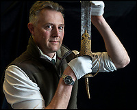 BNPS.co.uk (01202) 558833<br /> Pic: PhilYeomans/BNPS<br /> <br /> 'Once in a lifetime find' Auctioneer Anthony Cribb with the Tiger of Mysore's ornate gold encrusted sword.<br /> <br /> Stunning artefacts from Indian hero Tipu Sultan's fateful last stand have been rediscovered by the family of an East India Company Major who took part in the famous battle that ended his reign.<br /> <br /> And now Major Thomas Hart's lucky descendents are likely to become overnight millionaires after retrieving the historic items from their dusty attic.<br /> <br /> The fascinating treasures were taken from Tipu's captured fortress of Seringapatam in the wake of his defeat by British forces led by a young Duke of Wellington in 1799.<br /> <br /> The cache of ornate gold arms and personal effects even include's the battle damaged musket the Sultan used in his fatal last stand against the expanding British Empire in India.<br /> <br /> Tipu was last seen on the battlements of the fortress firing his hunting musket at the advancing British and after the fierce encounter his body was found bearing many wounds, including a musket ball shot above his right eye.<br /> <br /> The rediscovered musket, complete with battle damaged bayonet, has the distinctive tiger stripe pattern unique to the self styled Tiger of Mysore own weapons - and tellingly there is also shot damage to the lock and stock that may have been caused by the musket ball that finished him off.<br /> <br /> Also included in the sale are four ornate gold-encrusted sword's bearing the mark of Haider Ali Khan, Tipu's father and the previous ruler of independent Mysore, along with a solid gold &lsquo;betel casket&rsquo; complete with three 220 year old nuts still inside.<br /> <br /> The war booty was brought back to Britain by Major Thomas Hart of the British East India Company following the fourth and final Anglo-Mysore war.<br /> <br /> They have been passed down through the family ever since and now belong to a couple who have kept them wrapped in newspaper in the dusty attic of their semi-detached home for years.