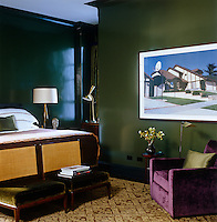 The bedroom is masculine and luxurious with deep green walls and richly textured upholstery