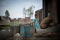 Indian children stands outside of their house in a slum in Moradabad district of the Northern Indian state of Uttar Pradesh, India on the 14th of February 2011.