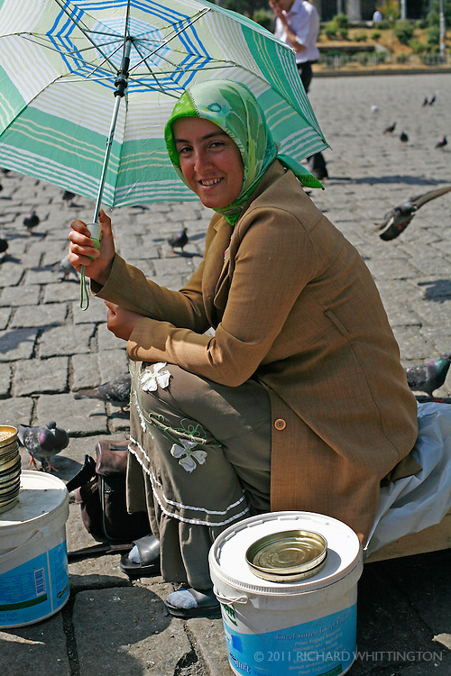 A Turkish woman sells seeds to feed to the pigeons in a town square in Istanbul, Turkey.