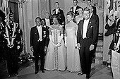 United States President John F. Kennedy and First Lady Jacqueline Kennedy stand in front of the Grand Staircase of the White House in Washington, DC prior to a dinner in honor of President of the Ivory Coast, Félix Houphouët-Boigny, and First Lady of the Ivory Coast, Marie-Thérèse Houphouët-Boigny on May 22, 1962. Front row (L-R): President Houphouët-Boigny; Mrs. Houphouët-Boigny; Mrs. Kennedy; President Kennedy. Others (L-R): Ambassador of the Ivory Coast, Henri Konan Bédié; U.S. Ambassador to the Ivory Coast, R. Borden Reams; Military Aide to President Kennedy, General Chester V. Clifton; Air Force Aide to President Kennedy, Brigadier General Godfrey T. McHugh; Virginia Rusk; U.S. Secretary of State Dean Rusk (mostly hidden); Naval Aide to President Kennedy, Captain Tazewell Shepard. <br /> Credit: Arnie Sachs / CNP