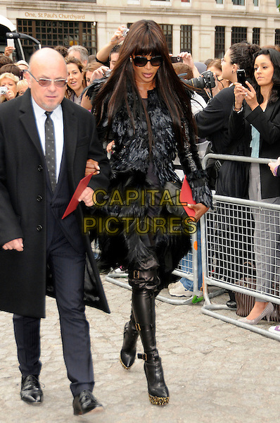 NAOMI CAMPBELL.Memorial service for Alexander McQueen, St. Paul's Cathedral, London.England..September 20th, 2010.full length black coat jacket boots tights sunglasses shades feather gold platform .CAP/CAS.©Bob Cass/Capital Pictures.