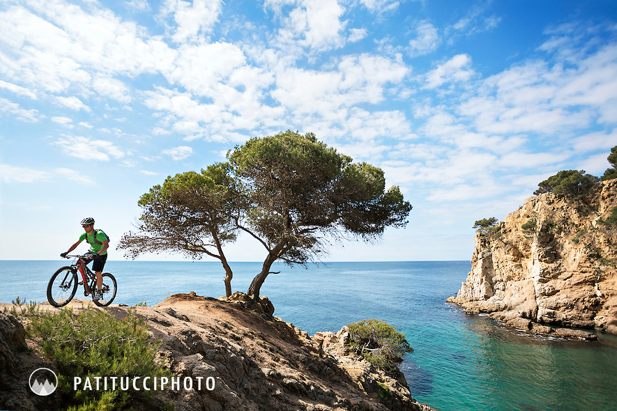A mountain biker riding along the Costa Brava above the Mediterranean coastline