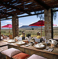 The terrace has an endless view over the Karoo veld and the Renosterberg and the rustic table is made up of railway sleepers that have been sawn in half and laid onto a stone base