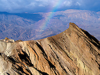 Rainbow, storm and rock formations as seen from Golden Canyon Trail. Death Valley National Park, California