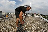 Etienne Herr greift sich eine weitere Querstange für die Plattform auf dem Dach der Robert-Bunsen-Straße 31