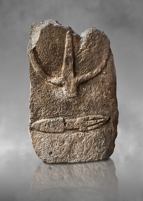 Late European Neolithic prehistoric Menhir standing stone with carvings on its face side. The representation of a stylalised male figure starts at the top with a long nose from which 2 eyebrows arch around the top of the stone. below this is a carving of a falling figure with head at the bottom and 2 curved arms encircling a body above. at the bottom is a carving of a dagger running horizontally across the menhir. Excavated from S'Arretzraxiu, Laconi. Menhir Museum, Museo della Statuaria Prehistorica in Sardegna, Museum of Prehoistoric Sardinian Statues, Palazzo Aymerich, Laconi, Sardinia, Italy