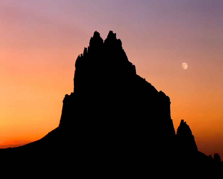 Sunset light and moonset over the silhouette of Shiprock; Navajo Nation, NM