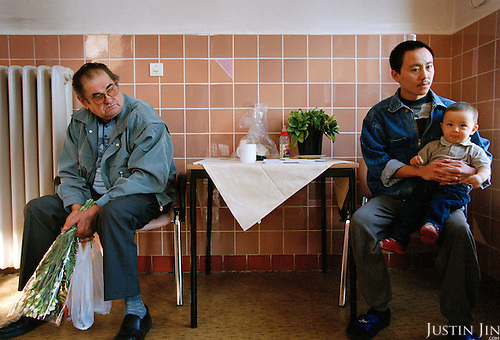 A German man stares at a sick Vietnamese asylum seeker and his son in a hospital in Guben, a German town in the state of Brandenburg on the Polish border....Photo by Justin Jin