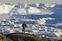 Hiker overlooking fiord covered with small pieces of ice and large icebergs, mid summer, June; Disko Bay, Greenland