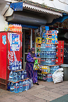 Essaouira, Morocco.  Woman Leaving Small Grocery and Sundries Shop.  Bottled Water Supplies around the Entrance.