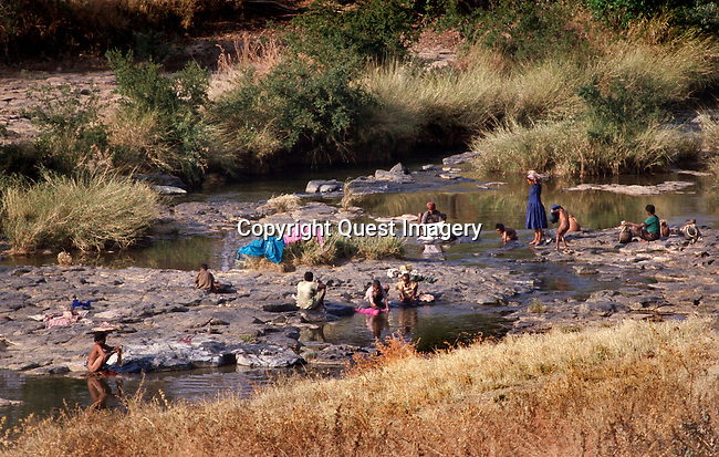 Natives bath and wash their clothes in the river near their remote village in southwestern Ethiopia's Sidamo Region. The river is their life-source as it also supplies them with their drinking and cooking water as well as irrigation for their subsistance crops in the harsh and barren land. <br />