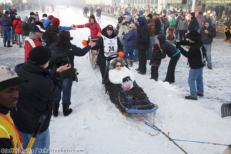 Ellen Halverson gets high-fives from the crowd as she passes them on 4th Avenue during the Iditarod 2014 Ceremonial start in downtown Anchorage, Alaska.<br /> <br /> Iditarod Sled Dog Race 2014<br /> PHOTO (c) BY JEFF SCHULTZ/IditarodPhotos.com -- REPRODUCTION PROHIBITED WITHOUT PERMISSION