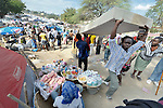 Two men carry a mattress through a camp for homeless families set up on a golf course in Port-au-Prince, Haiti, which was ravaged by a January 12 earthquake.