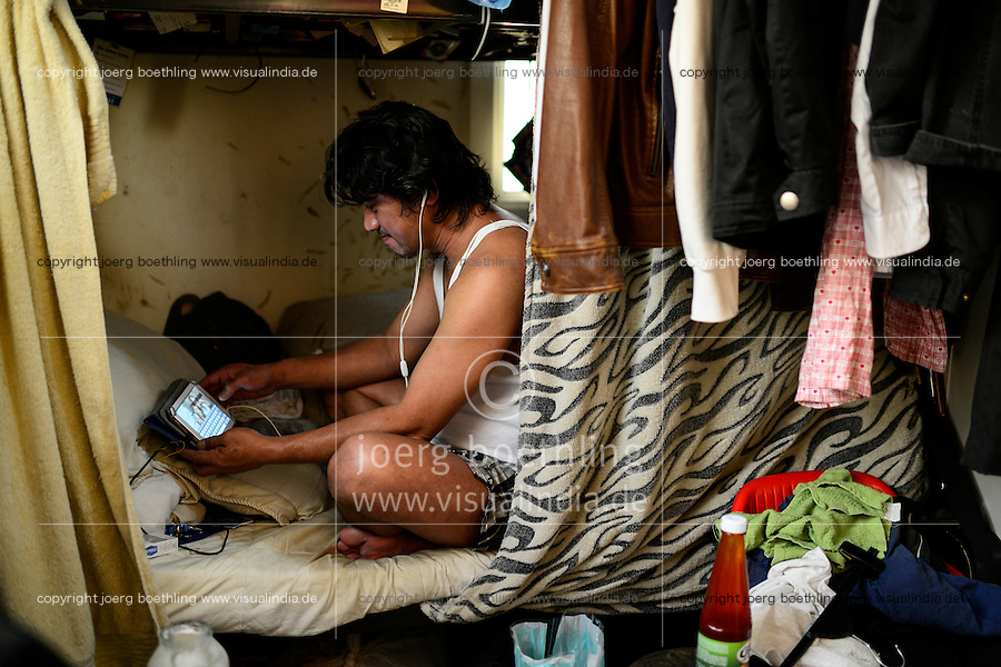 QATAR, Doha, housing complex for migrant worker outside the city, six filipino worker share a 10 square meter room / KATAR, Doha, Sammelunterkunft fuer Gastarbeiter, sechs philippinische Gastarbeiter muessen sich einen zehn Quadratmeter grossen Raum teilen, Arbeiter Noel kommuniziert mit seiner Familie in Manila