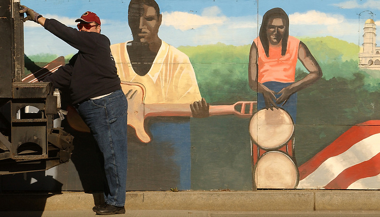 "A worker unloads a truck at a Centex Constuction Company site a 3rd and Const., NW.  The mural that surrounds the site for the new annex for the U.S. Courts, District of Columbia, was done by kids from Sierra Leone depicting a historic timeline of that country.  It is titled ""What Freedom Means to Me."""