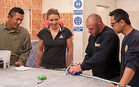 Instructor with trainee tilers,  Able Skills training centre, Dartford, Kent.