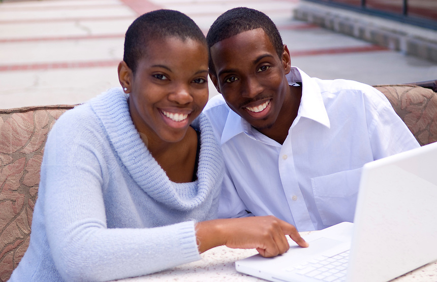 Black African American couple working together on computer outdoors in business