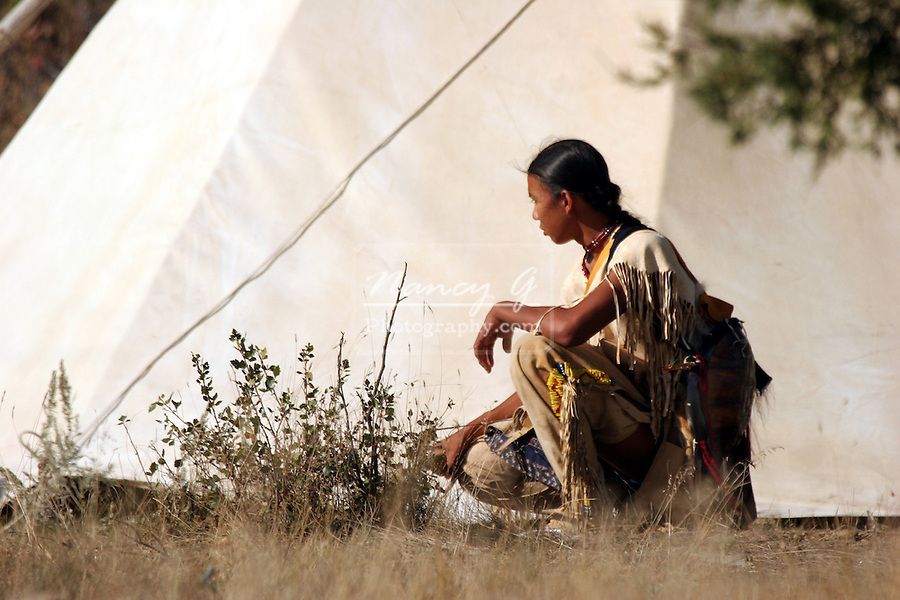 A Native American Indian boy kneeling by a tipi