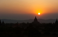 The sun sets over the Irrawaddy River and the hills behing Bagan in Myanmar, silhouetting some of the thousands of pagodas on the surrounding plain.