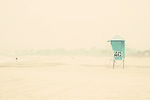 a lone person & a lifeguard tower stand out against the backdrop of fog on a california beach