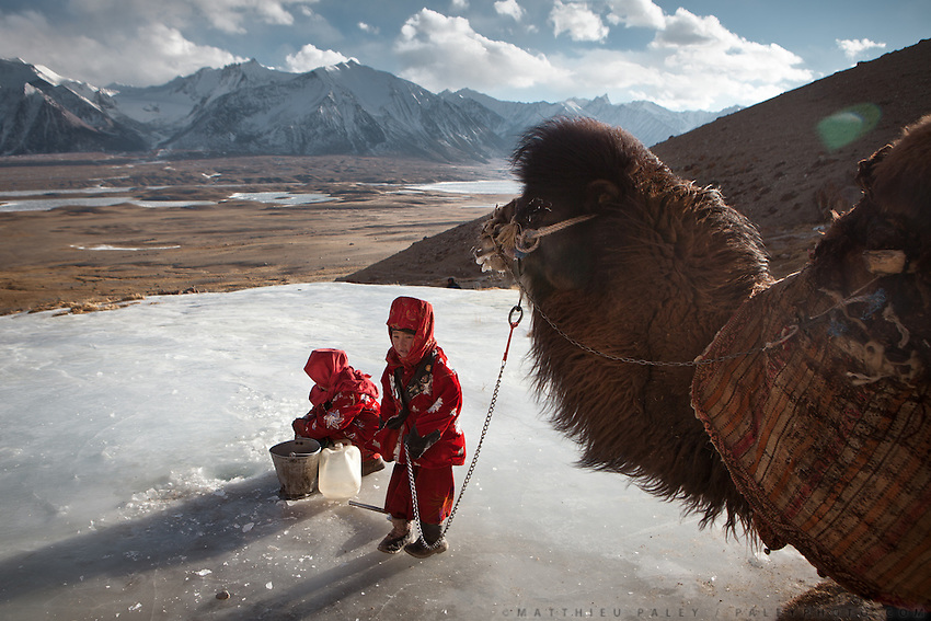 Two young Kyrgyz girls fetching water with a Bactrian camel.  They need to break the ice to get to the spring..Ech Keli, Er Ali Boi's camp, one of the richest Kyrgyz in the Little Pamir..Trekking with yak caravan through the Little Pamir where the Afghan Kyrgyz community live all year, on the borders of China, Tajikistan and Pakistan.