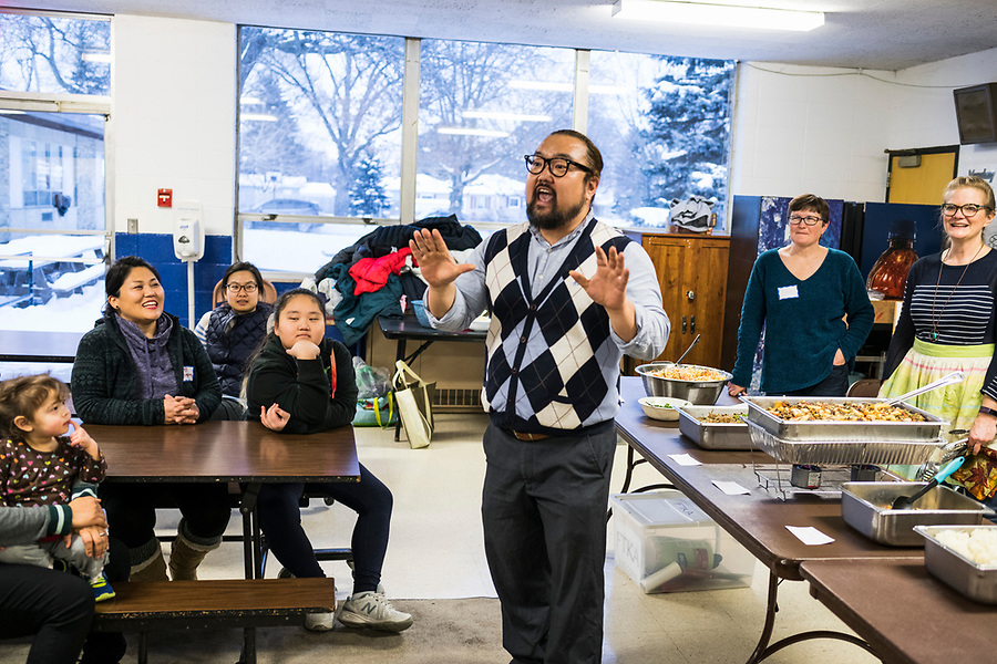 "Jaekwan Yum teaches guest how to say ""happy new year"" in Korean during a lunar new year event hosted by Families Through Korean Adoption (FTKA) in the gym and school cafeteria of St. Dennis Church in Madison, Wis., on Feb. 10, 2018. The event celebrated the passing of the lunar new year, and is one of several events for FTKA-member families and children to gather and enjoy cultural fun, food and play. (Photo by Jeff Miller - www.jeffmillerphotography.com)"