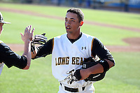 Tristan Mercedes (23) of the Long Beach State Dirtbags is greeted by a teammate during a game against the Arizona State Sun Devils at Blair Field on February 27, 2016 in Long Beach, California. Long Beach State defeated Arizona State, 5-2. (Larry Goren/Four Seam Images)