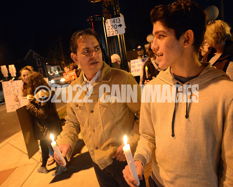 From left, Khawar Kalim and Elie Kalim, 14 of Newtown, Pennsylvania hold lit candles during a candlelight vigil, as a sign of solidarity for the victims of last week's terror attack in California, Friday December 11, 2015 in Langhorne, Pennsylvania. (Photo by William Thomas Cain)