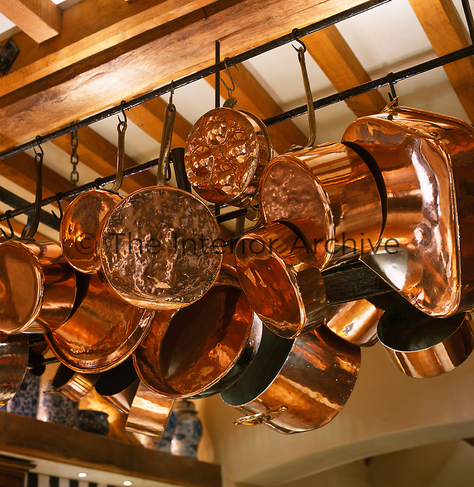 In this traditional kitchen a warm glow is reflected from a collection of copper pans hanging from the beamed ceiling