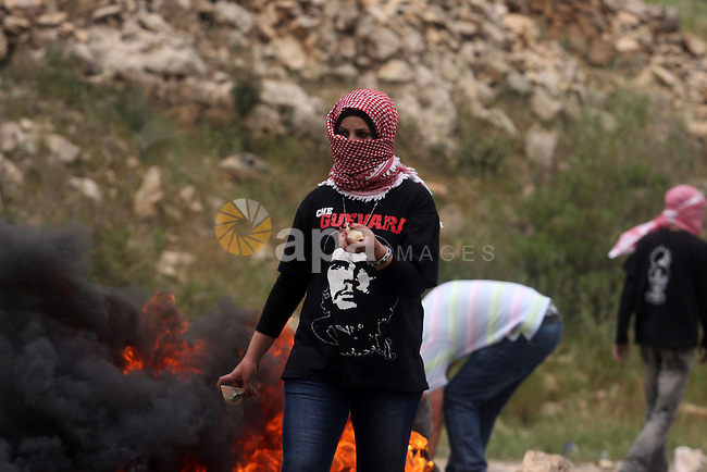 "Palestinian protesters throw stones at Israeli troops during a demonstration outside Ofer military prison near the West Bank city of Ramallah on May 1, 2012 in a show of support for prisoners held in Israeli jails. Clashes erupted between stone-throwing youths and the Israeli army, who fired tear gas, rubber bullets and a foul-smelling liquid known as ""skunk"" to break up the demonstration. Photo by Issam Rimawi"