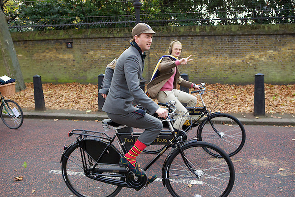 Fredrik Ferrier gives a v-sign while cycling on The Tweed Run with Francis Boulle