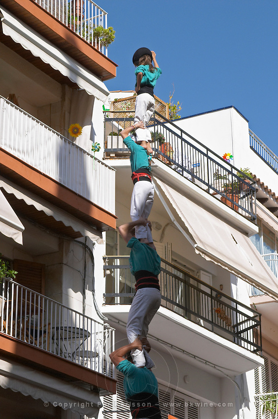 Human tower competition, castellers,  Child on top raises hand: finished. Sitges, Catalonia, Spain