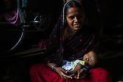 Maina Devi is seen with her 3 month old daughter, Priya in her hut in Bhelaiya village in Raxaul, Bihar, India.