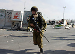 An Israeli border police officer chases Palestinian stone-throwers during clashes at the Kalandia checkpoint near the West Bank city of Ramallah October 9, 2009. Palestinian leaders on Thursday called for a one-day general strike and warned of more street protests over Jerusalem, where clashes at the flashpoint al-Aqsa mosque two weeks ago cranked up tensions in the disputed city. Israel is playing down Palestinian warnings that its security tactics risk a new Palestinian uprising. Photo by Issam Rimawi