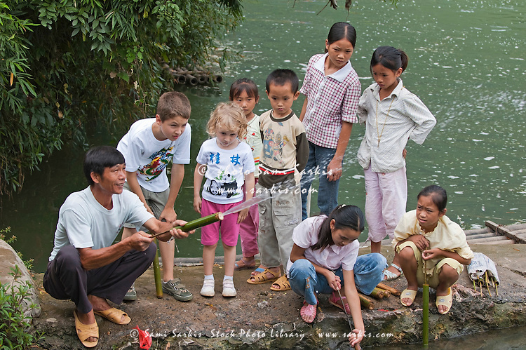 Man demonstrating his bamboo water gun to the European and Chinese kids around him, Yangshuo, Guangxi, China.