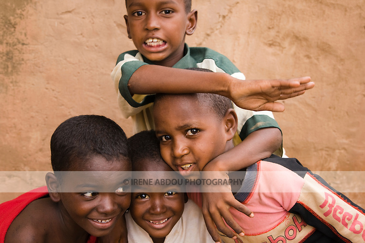 Four children from the traditionally pastoralist Fulani ethnic group playfully pose for the camera in Ouagadougou, Burkina Faso.